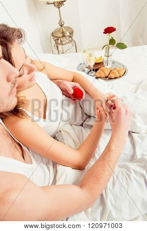 Man Making Proposal Of Marriage To His Girlfriend In Bedroom