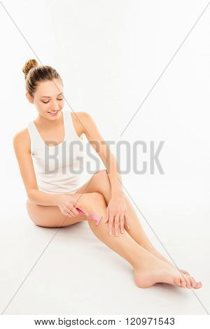 Pretty Sexy Young Woman Shaving Her Leg On White Background