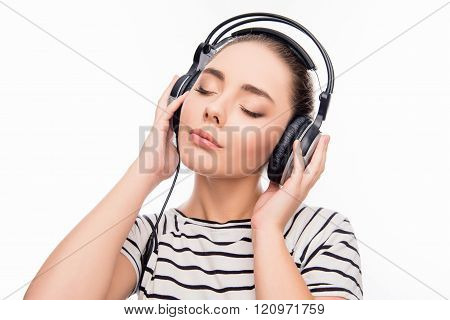 Pretty Girl Listening Music With Closed Eyes And Touching Headphones