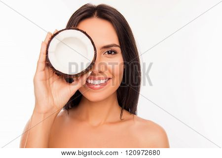 Cheerful Pretty Young Woman Holdind Coconut Near Her Eyes
