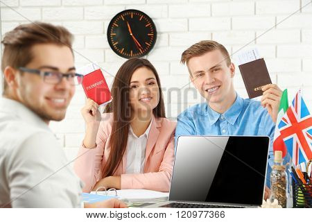 Agent and happy young couple with passports and tickets in the office of travel company