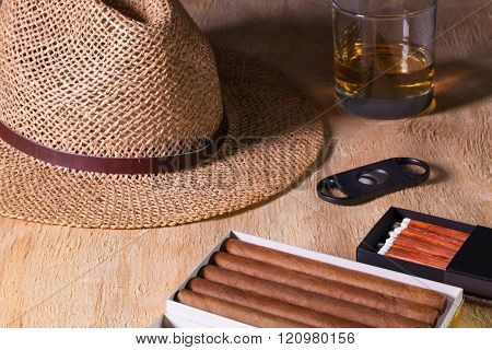 Siesta - cigars straw hat and Scotch whiskey on a wooden table