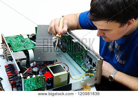 A Man With A Soldering Iron To Repair The Device