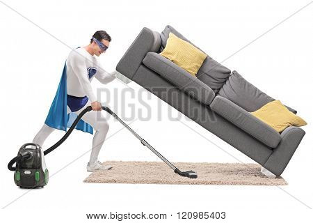 Profile shot of a strong man in superhero costume vacuuming under a sofa isolated on white background