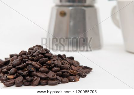 coffee beans in the foreground with espresso maker