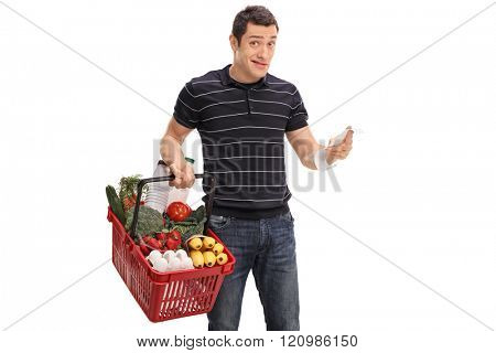 Discontent young man holding a shopping bill and looking at the camera isolated on white background