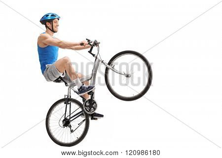 Young cyclist performing a wheelie with a bicycle isolated on white background