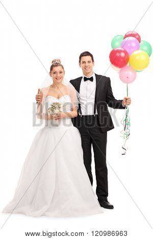 Full length portrait of a young newlywed couple holding a bunch of balloons and posing together isolated on white background