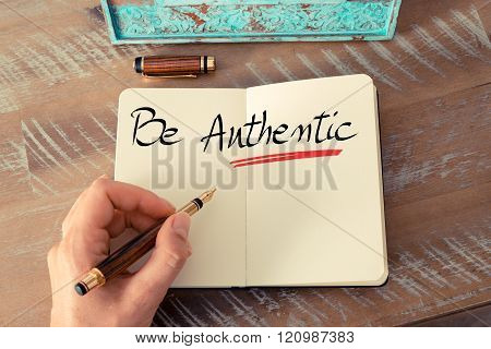 Retro effect and toned image of a woman hand writing a note with a fountain pen on a notebook. Handwritten text Be Authentic as business concept image