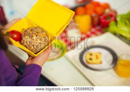 Girl Holding A Lunch Box In The Kitchen