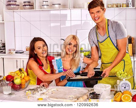 Two young women  and one man baking cookies in oven. Small group people.