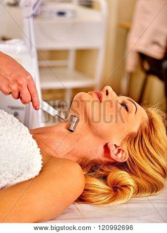 Young woman enjoying electric galvanic neck spa massage at beauty salon.