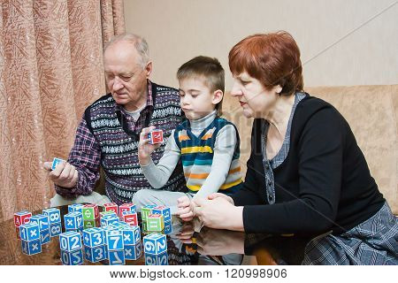 A Grandmother And Grand-dad Play With A Grandchild In Blocks