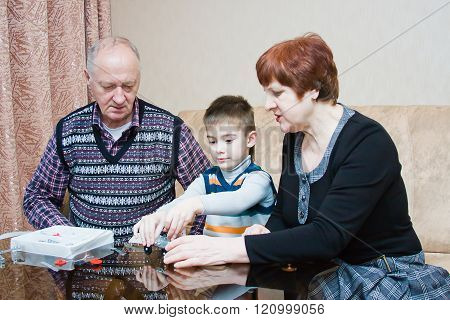 A Grandmother, Grand-dad, Play With A Grandchild In A Designer