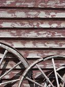 foto of wagon wheel  - painted wall with two wagon wheels leaning up against it - JPG