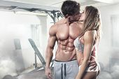 Beautiful Young Sporty Kissing Sexy Couple In Gym poster