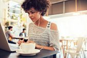 Attractive Young Woman With Earphones Using Laptop At Cafe poster