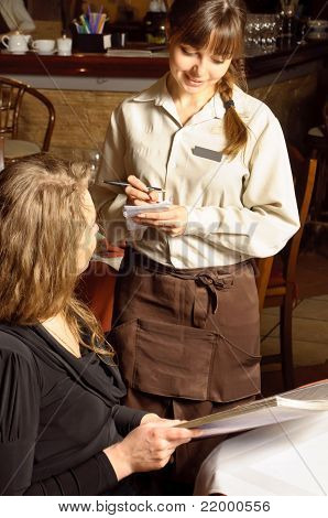 Beautiful woman in restaurant. Waiter is taking the order