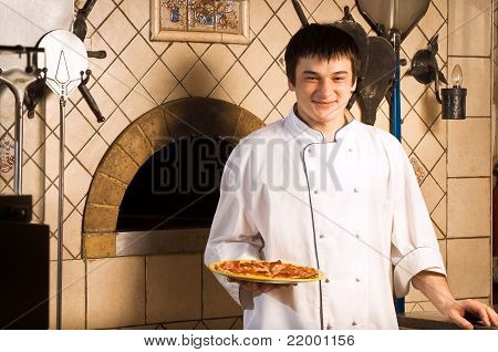 A Young Chef Standing Next To Oven