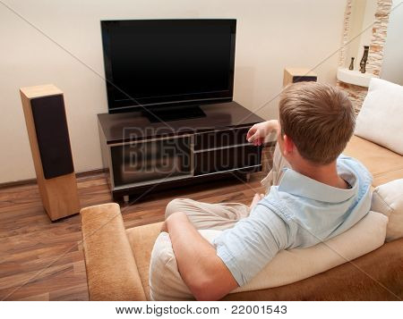 Man lying on sofa watching TV at home.