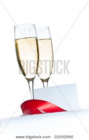 Glasses with Champagne and blank invitation card isolated