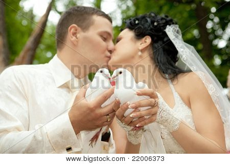 Beautiful newlyweds  kissing holding white doves in hands