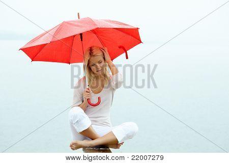 Portrait of sad young woman sitting with umbrella under rain