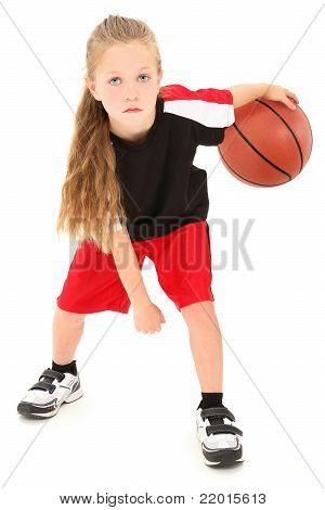 Serious Girl Child Basketball Player Dribbling Ball Between Legs
