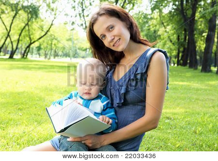 Portrait of little boy reading a book in the park with her mother