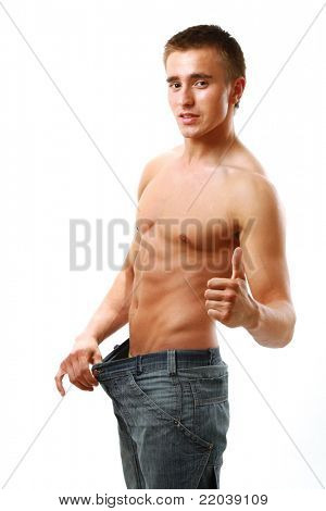 A muscular man showing how much weight he lost