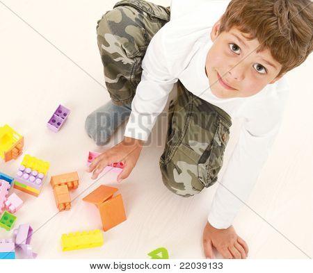 Un niño está jugando con mirando hacia arriba, aislado sobre fondo blanco, vista superior