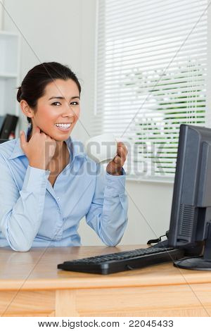 Beautiful woman enjoying a cup of coffee while looking at a computer screen at the office