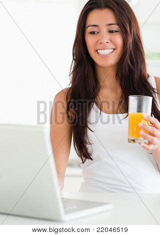 Pretty woman relaxing with her laptop while holding a glass of orange juice in the kitchen