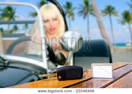 Llaves del coche en mesa con chica rubia conduciendo coche deportivo en palm beach de árboles
