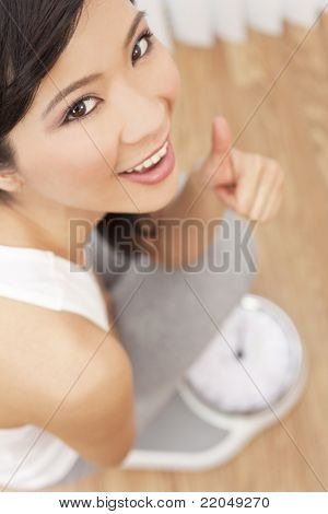 Over head view of happy & beautiful Oriental Asian Chinese woman weighing herself on scales at gym or health club and giving a successful thumbs up