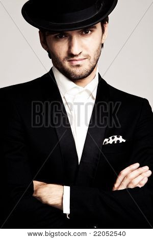 elegant young man in black tuxedo and derby,portrait, studio shot