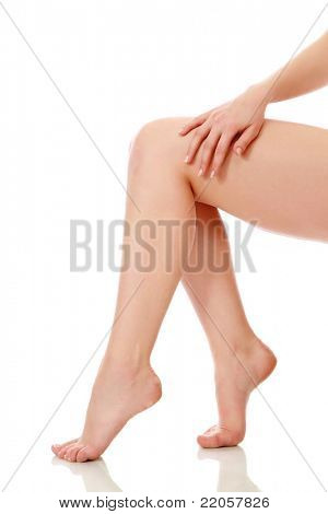 A hand touching beautiful woman's legs, isolated on white