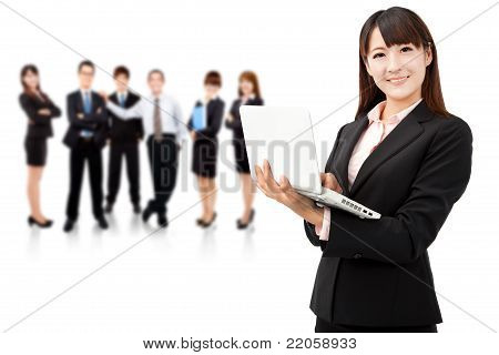 smiling businesswoman holding laptop and successful business team