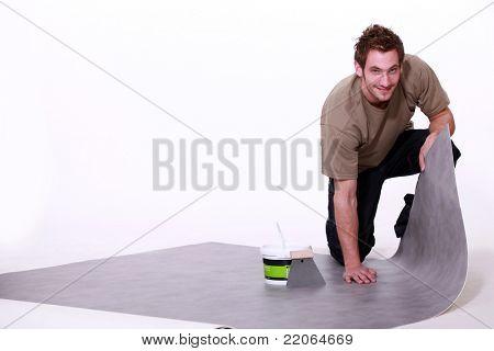 Man putting down linoleum flooring