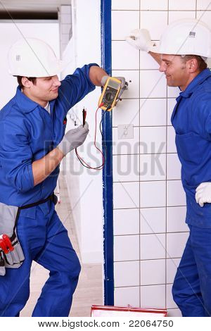 Two electricians discussing a voltmeter