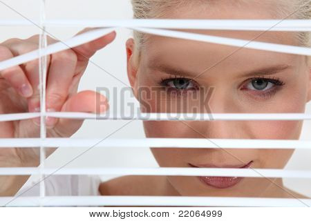 a blonde woman looks through blinds