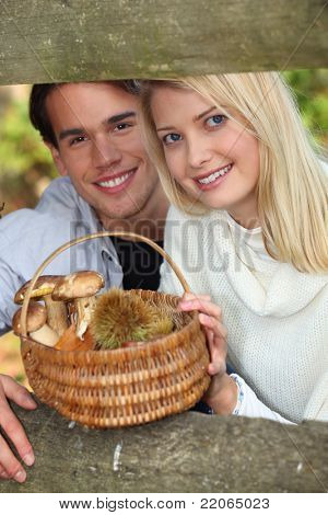 Couple collecting mushrooms and chestnuts in the forest