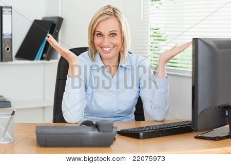 Smiling Blonde Woman Sitting Behind Desk Not Having A Clue What To Do Next