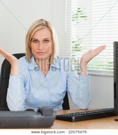Serious Woman Sitting Behind Desk Not Having A Clue What To Do Next
