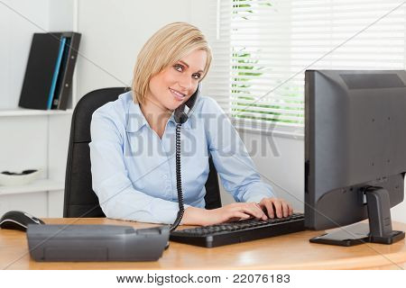 Working Businesswoman On The Phone While Typing Looks Into Camera