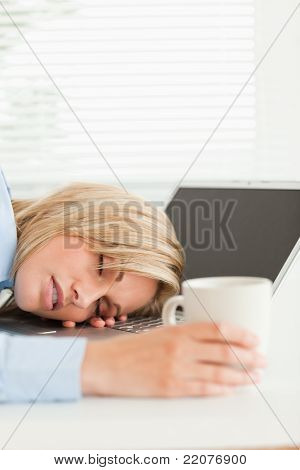Gorgeous Blonde Woman Sleeping On Her Notebook Holding Cup Of Coffee