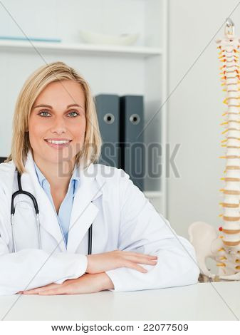Smiling Doctor With Model Spine Next To Her Looks Into Camera
