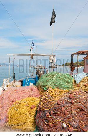 Redes de pesca griego y barco en el puerto de Nea Epidauro