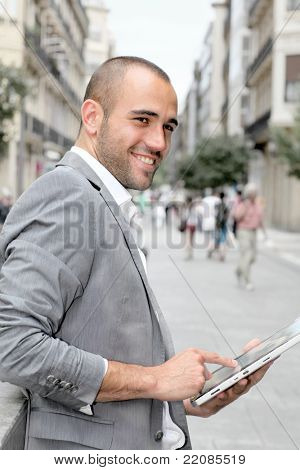 Man with suit jacket using touch pad in town
