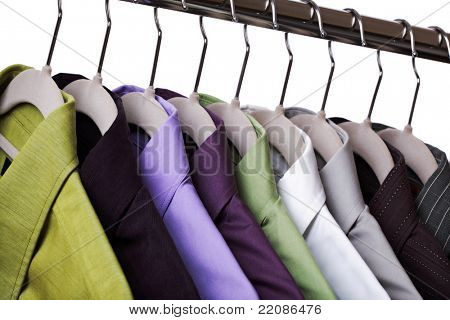 Multi colored shirts on hangers against a white background